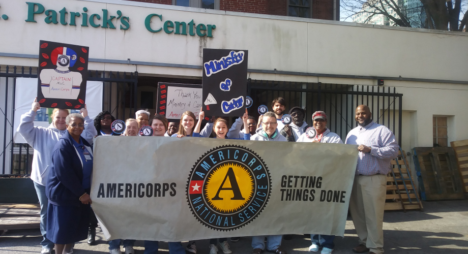Staff and Volunteers Holding AmeriCorps Banner and Posterboards